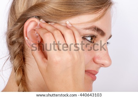 Portrait of a beautiful young woman inserting a hearing aid