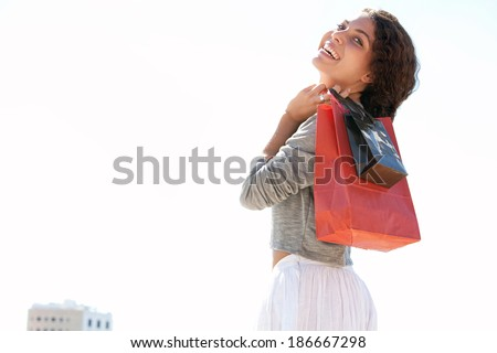 Portrait of a beautiful young woman joyfully walking with shopping bags against a sunny sky on a holiday trip, turning and smiling at the camera during a summer day. Consumer and travel lifestyle.