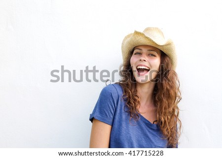 Portrait of a beautiful young woman laughing with cowboy hat against white background  - stock photo