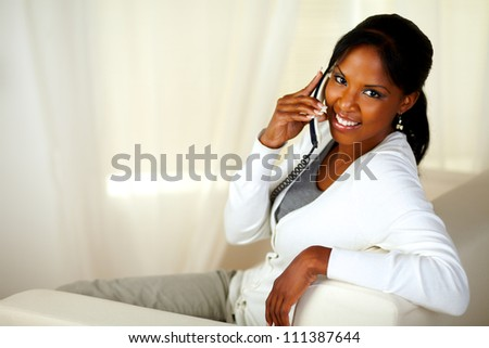 Portrait of a beautiful young woman looking at you while conversing on phone. With copyspace
