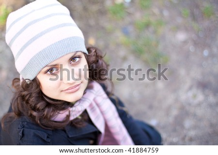 Portrait of a beautiful young woman looking upside outdoors.