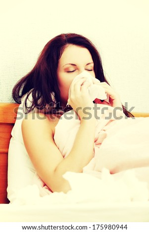 Portrait of a beautiful young woman lying in bed, having a cold and sneezing in a tissue. - stock photo