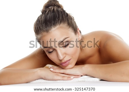 portrait of a beautiful young woman lying on a white background - stock photo