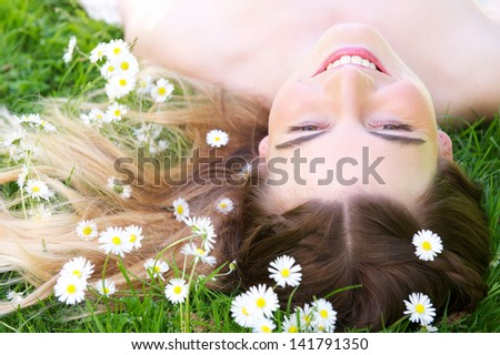 Portrait of a beautiful young woman lying on grass with flowers in the park - stock photo