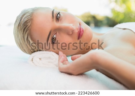 Portrait of a beautiful young woman lying on massage table at spa center - stock photo