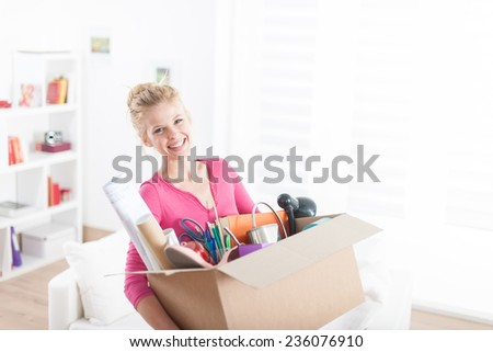 portrait of a beautiful young woman moving in  a new apartment and carrying a box with various objects - stock photo
