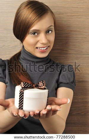 Portrait of a beautiful young woman offering a present. Office background.