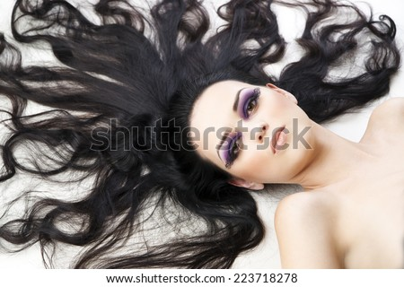Portrait of a beautiful young woman on a white background. Professional make-up and hairstyle.