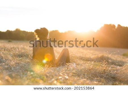Portrait of a beautiful young woman or girl on meadow watching the sunset enjoying nature summer evening outdoors. Soft red light. Sunshine. - stock photo