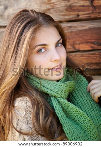 Portrait of a beautiful young woman outdoor on a chilly day against a wooden wall. - stock photo