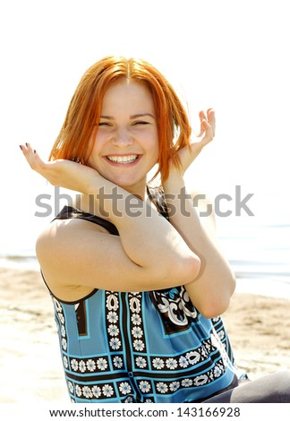 Portrait of a beautiful young woman outside sitting on the beach smiling