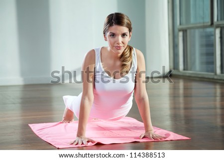 Portrait of a beautiful young woman practicing yoga on mat at gym