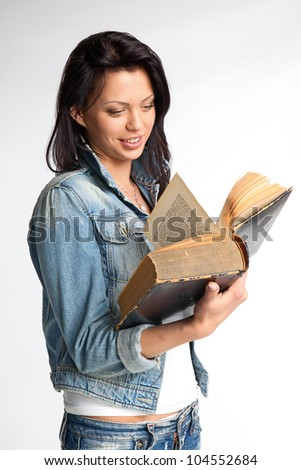 Portrait of a beautiful young woman reading a book - stock photo