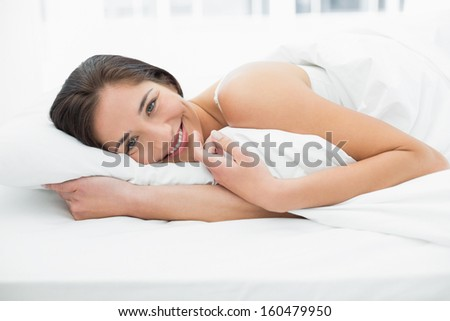 Portrait of a beautiful young woman resting in bed