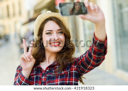 Portrait of a beautiful young woman selfie in the street with a smartphone. Young woman wearing plaid shirt and sun hat with red lips in urban background.