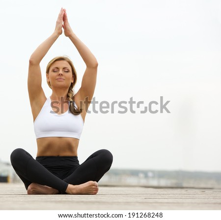 Portrait of a beautiful young woman sitting in yoga pose outdoors - stock photo