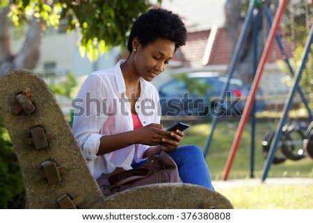 Portrait of a beautiful young woman sitting on park bench sending text message on cell phone outdoors - stock photo
