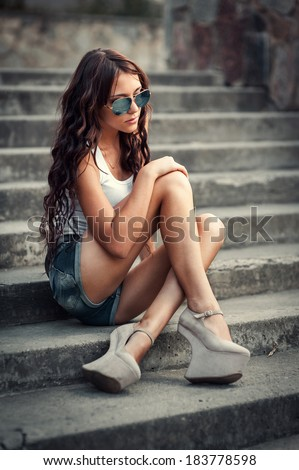 Portrait of a beautiful young woman sitting on stairs outdoors. beautiful young woman smiling. young woman in colorfull summer clothes sit on stairs outdoor shot - stock photo