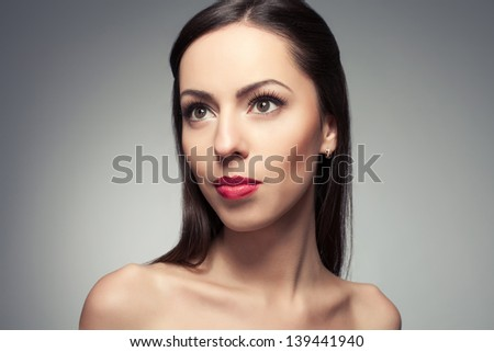Portrait of a beautiful young woman smiling and posing over light-gray background. Healthy skin. Copyspace. Studio shot - stock photo