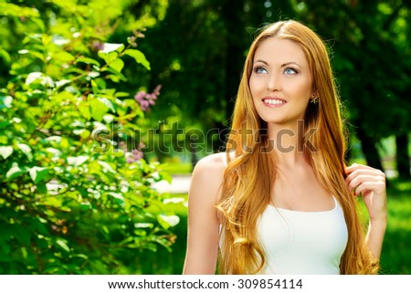 Portrait of a beautiful young woman smiling to a sunny summer day. She is absolutely happy. Beauty, fashion. - stock photo