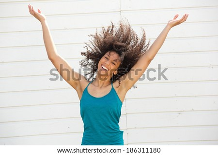 Portrait of a beautiful young woman smiling with arms spread open - stock photo