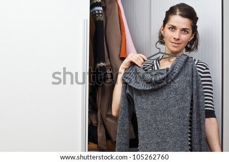 Portrait of a beautiful young woman standing at her wardrobe trying to choose a piece of clothes, smiling into camera - stock photo