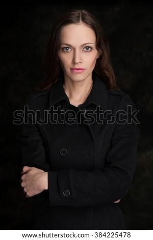 Portrait of a beautiful young woman. Studio, dark background. - stock photo