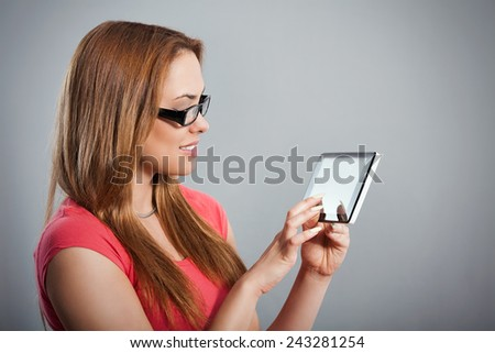 Portrait of a beautiful young woman touching screen of a digital tablet. Studio Shot. - stock photo