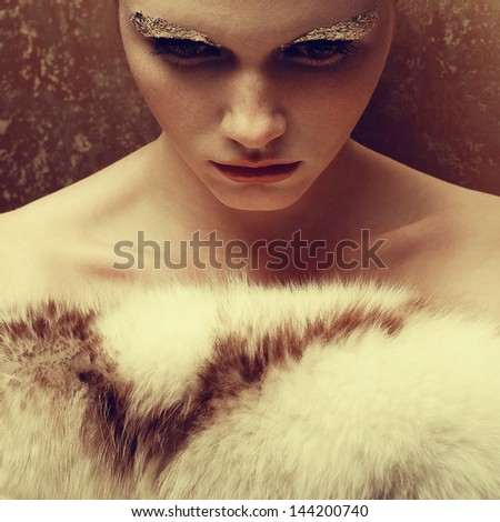 Portrait of a beautiful young woman undressed holding luxurious fur coat after ball. Arty make-up of golden foil. Femme fatale. Vintage (old hollywood) style. Healthy skin. Studio shot - stock photo