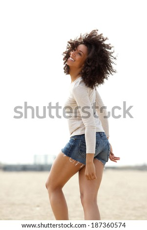 Portrait of a beautiful young woman walking and smiling outdoors - stock photo
