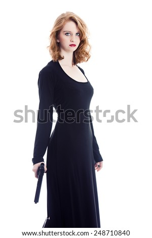 Portrait of a beautiful young woman wearing a black gown and holding a gun.  Isolated on white. - stock photo