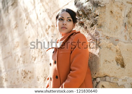 Portrait of a beautiful young woman wearing an orange coat while on vacation surrounded by old stone walls and looking away from the camera, being thoughtful. - stock photo