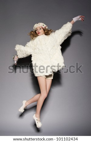 Portrait of a beautiful young woman wearing fur coat. Over gray background. - stock photo