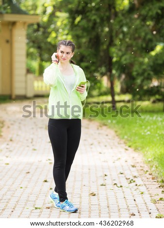 Portrait of a beautiful young woman while is going to a walk and listening to a music.