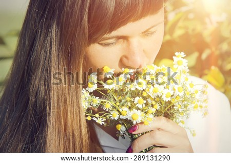 Portrait of a beautiful young woman with a bouquet of daisies - stock photo