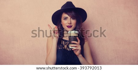 portrait of a beautiful young woman with a cup of coffee standing on the pink background