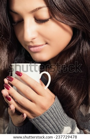 Portrait of a beautiful young woman with a cup of hot coffee in his hands. - stock photo