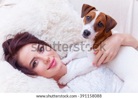 portrait of a beautiful young woman with a dog lying on the sofa - stock photo
