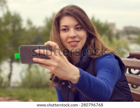 Portrait of a beautiful young woman with a mobile phone outdoors.