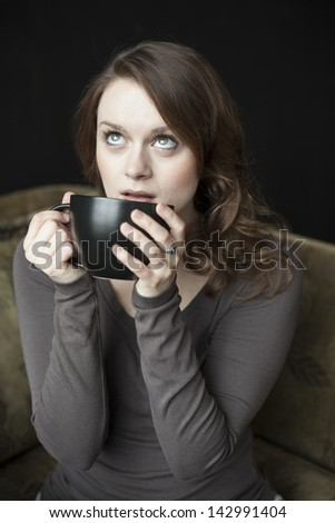 Portrait of a beautiful young woman with beautiful green eyes and brown hair holding a black coffee cup. - stock photo