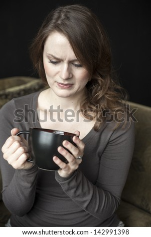 Portrait of a beautiful young woman with beautiful green eyes and brown hair making an ugly facial expression while she holds a black coffee cup. - stock photo