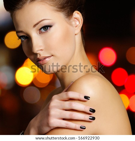 Portrait of a beautiful young woman with black nails - stock photo