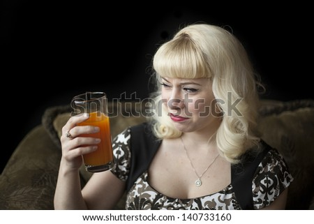 Portrait of a beautiful young woman with blond hair drinking a glass of mango juice. - stock photo