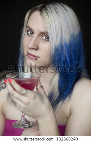 Portrait of a beautiful young woman with blue hair and pink dress holding a pink martini.
