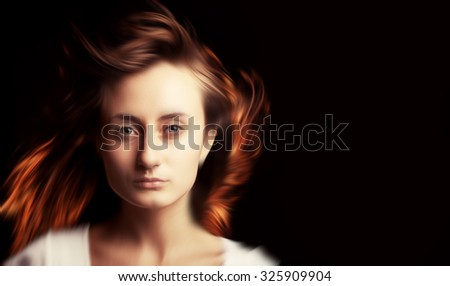 Portrait of a beautiful young woman with blurred hair on a dark background with copy-space. Intentional color shift and motion blur