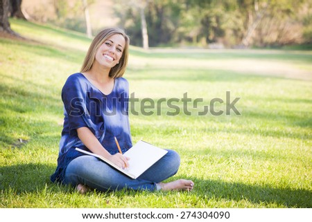 Portrait of a Beautiful Young Woman With Book Outdoors at the Park. - stock photo