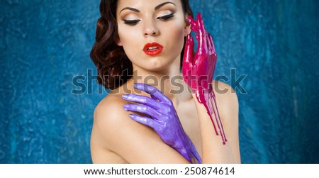 Portrait of a beautiful young woman with bright make up and colored splashes hands - stock photo