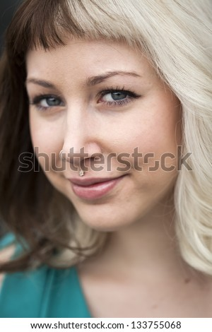 Portrait of a beautiful young woman with brown and blond hair looking right into the camera.