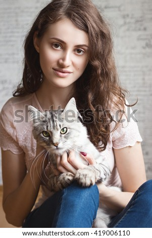 Portrait of a beautiful young woman with cat on her lap. No makeup. Natural beauty concept