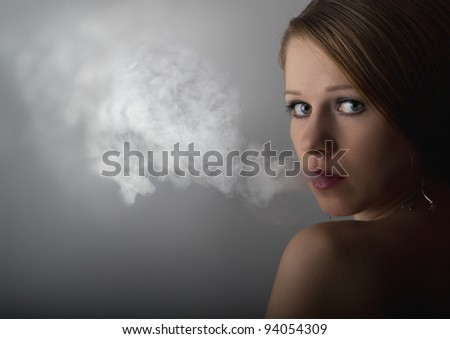 portrait of a beautiful young woman with cigarette smoke on a dark gray background - stock photo